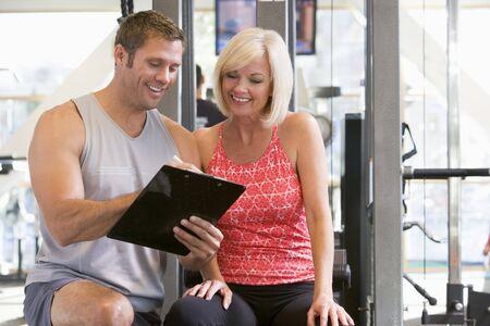 aide � la personne: Personal Trainer Talking To Woman Au Gym Banque d'images