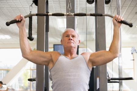 weight machine: Man Weight Training At Gym Stock Photo