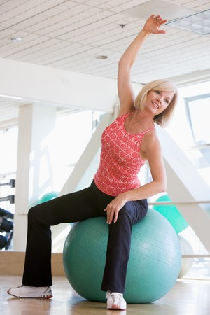 ball stretching: Woman Stretching On Swiss Ball At Gym