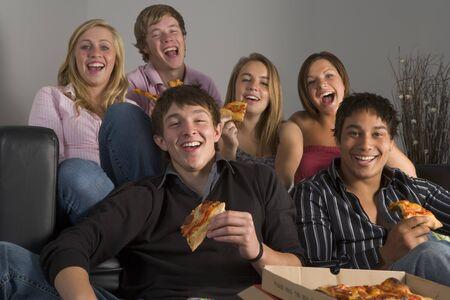 Los adolescentes se divierten y comer pizza