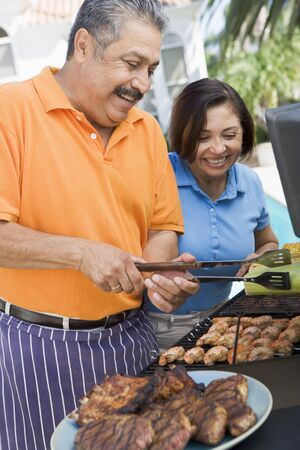 Couple Cooking On A Barbeque Stock Photo - 4499877