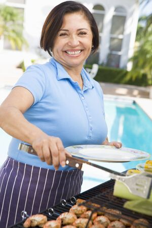 Woman Cooking On A Barbeque photo