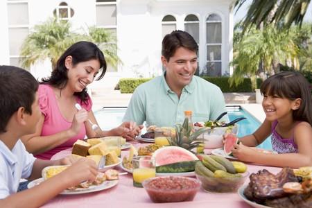 una familia comiendo: Disfrutar de un asado familiar Foto de archivo