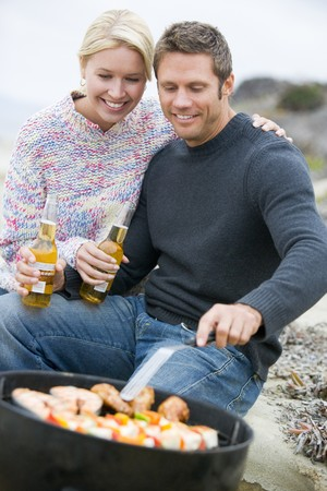 Couple Cooking On A Barbeque Stock Photo - 4499884