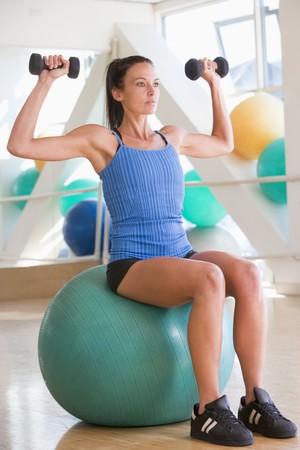 ropa deportiva: La mujer usando la mano de pesos en la Pelota Suiza en el gimnasio