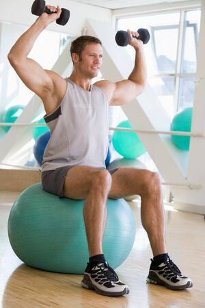 swiss ball: Man Using Hand Weights On Swiss Ball At Gym