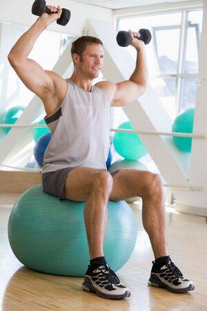 swiss ball: Man Using Hand Weights On Swiss Ball At Gym
