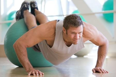 Man Balancing On Swiss Ball At Gym photo