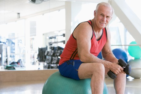 one senior adult man: Man Using Hand Weights On Swiss Ball At Gym