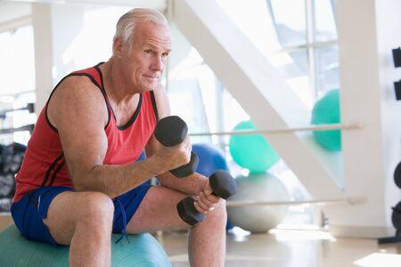 pesas: Hombre con pesas de mano en Suiza Ball en el gimnasio Foto de archivo