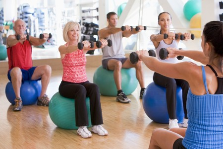 adult class: Instructor Taking Exercise Class At Gym Stock Photo