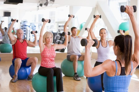hand weight: Instructor Taking Exercise Class At Gym Stock Photo