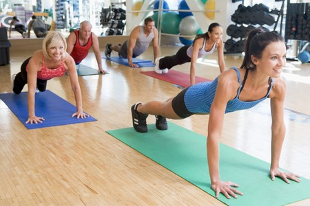 fitness instructor: Instructor Taking Exercise Class At Gym Stock Photo