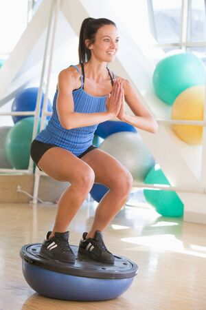 Woman Using On Balance Trainer At Gym photo