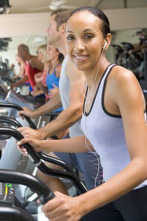 escucha activa: Woman Running on Treadmill en el gimnasio Foto de archivo