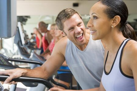 Personal Trainer Encouraging Woman Using Treadmill At Gym Stock Photo - 4499172