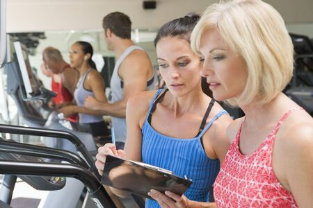 instructing: Personal Trainer Instructing Woman On Treadmill