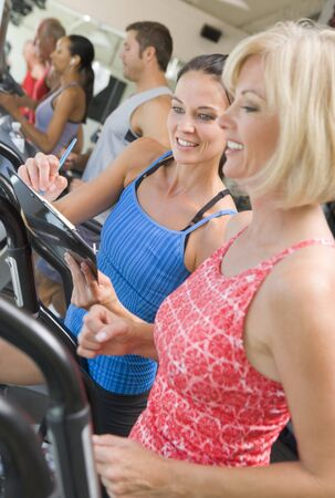 Personal Trainer Instructing Woman On Treadmill photo