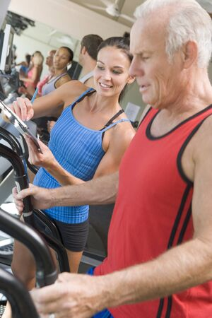 Personal Trainer Instructing Man On Treadmill photo