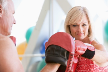 Woman Boxing With Personal Trainer At Gym photo