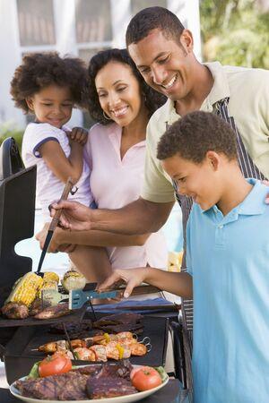 hombre cocinando: Familia disfrutando de un asado
