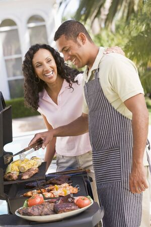 Couple Cooking On A Barbeque Stock Photo - 4499793