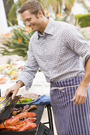 barbequing: Man Barbequing In A Garden
