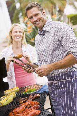 jasschort: Paar koken op een barbecue Stockfoto