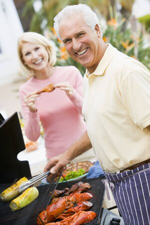Couple Cooking On A Barbeque Stock Photo - 4499401