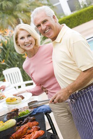 Couple Cooking On A Barbeque Stock Photo - 4499725