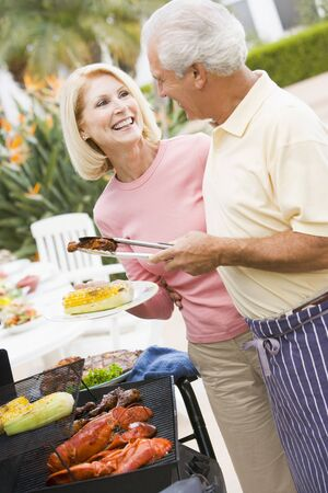 Couple Cooking On A Barbeque Stock Photo - 4499461