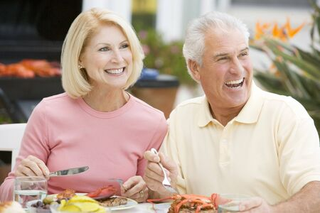 Couple Enjoying A Barbequed Meal In The Garden Stock Photo - 4499379