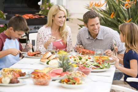 outdoor eating: Family Enjoying A Barbeque Stock Photo