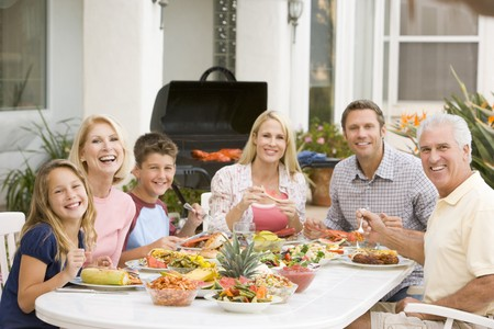 outside of house: Family Enjoying A Barbeque Stock Photo