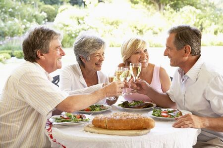 al: Friends Eating An Al Fresco Lunch, Holding Wineglasses Stock Photo