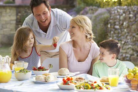 familia comiendo: Una familia Comer Al Fresco de alimentos Foto de archivo