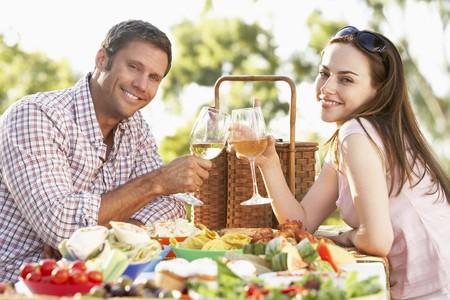 pareja comiendo: Un joven Comer Al Fresco de alimentos, Tostado Con vino Foto de archivo