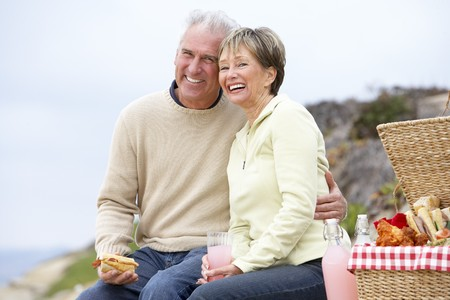 filled roll: Couple Eating An Al Fresco Meal At The Beach Stock Photo
