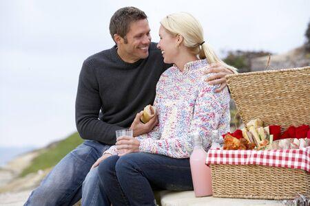 pareja comiendo: Pareja comer una comida al fresco en la playa