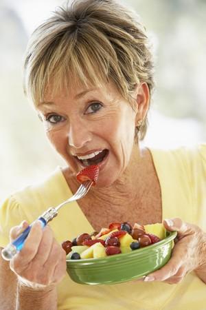 salade de fruits: Senior Femme Eating Fresh Fruit Salad Banque d'images