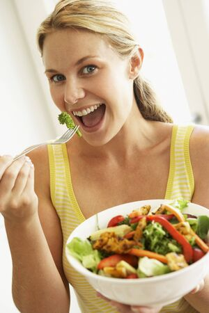 Mid Adult Woman Eating A Healthy Salad photo