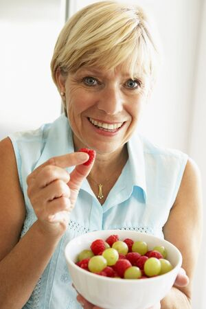 Middle Aged Woman Eating A Bowl Of Fruit photo