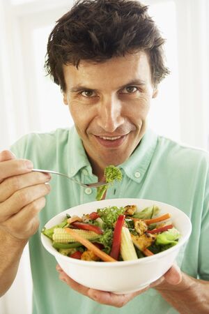 mid adult man: Media de Adultos Hombre comer una ensalada saludable Foto de archivo