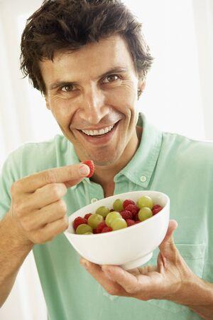 mid adult man: Mid Adult Man Eating Fresh Fruit