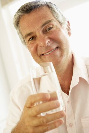 man drinking water: Middle Aged Man Drinking A Glass Of Water