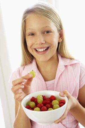Young Girl Eating Fresh Fruit Salad photo