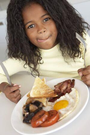 ni�a comiendo: Muchacha Comer Desayuno poco saludables Foto de archivo