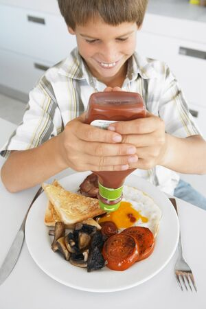 bacon portrait: Young Boy Eating Unhealthy Fried Breakfast Stock Photo