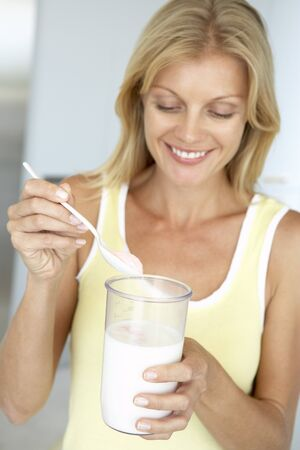 dietary supplements: Mid Adult Woman Holding Dietary Supplements