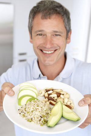 hombre comiendo: Mid Adult Man Holding plato de comida sana Foto de archivo